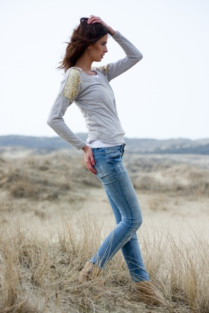 Beautiful young woman wearing a grey shirt and jeans posing in the dunes Stock Photo
