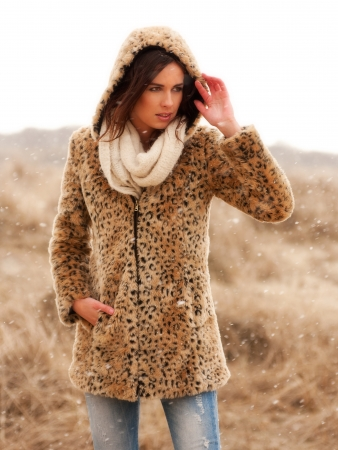 Beautiful young woman wearing a tigerprint coat and white scarf in the snow Stock Photo - 20222858