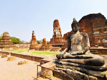 Ancient temples of Ayutthaya with statue in foreground and blue sky, Ayutthaya, Thailand - 2-7-2020
