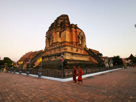 Wat Chedi Luang temple at dusk with monks passing by, Chiang Mai, Thailand