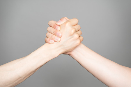 sh: Hand holding hand isolated over gray background - Friendship, Sh Stock Photo