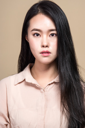 expressionless: Studio shot of young asian woman portrait - isolated