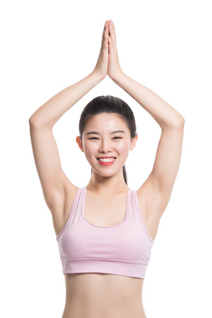 Studio portrait of twenties Asian woman doing yoga