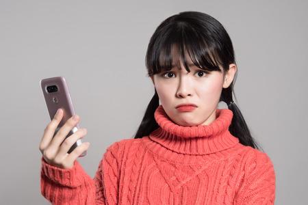 전화로 짜증 난 20 대 아시아 여성의 스튜디오 초상화
