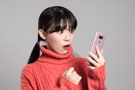 telephone interview: A studio portrait of a twenties Asian woman with a surprised look on the phone Stock Photo