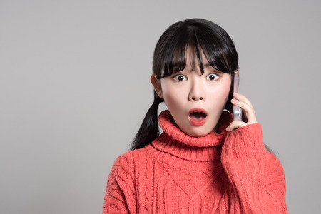 スタジオ ポートレート、20 代のアジアの女性の携帯電話に驚いた様子で 写真素材