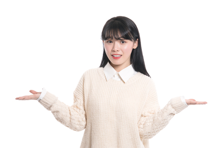 A studio portrait of a twenties Asian woman pointing at something and confidently introducing Фото со стока
