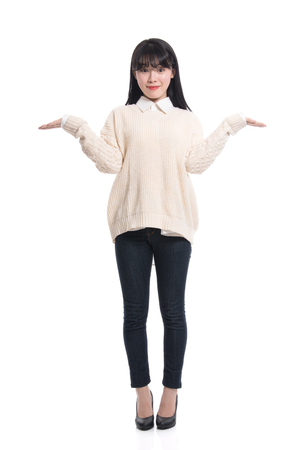20 years old: A studio portrait of a twenties Asian woman pointing at something and confidently introducing Stock Photo