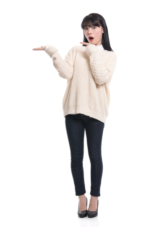 A studio portrait of a twenties Asian woman pointing at something and confidently introducing Stock Photo