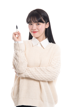 20 year old: Studio portrait of twenties Asian woman writing something with a pen