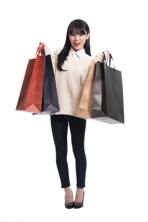 Studio portrait of twenties Asian woman happily shopping