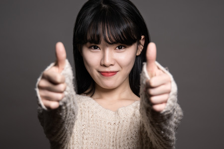 20 year old: Studio portraits of happy twenties Asian women with thumbs up Stock Photo