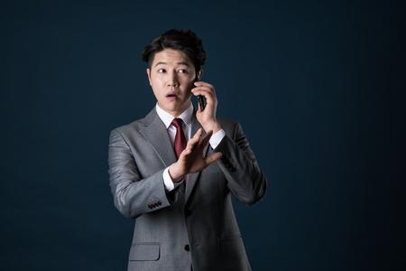 suspicion: East Asian Businessman shooting studio portrait