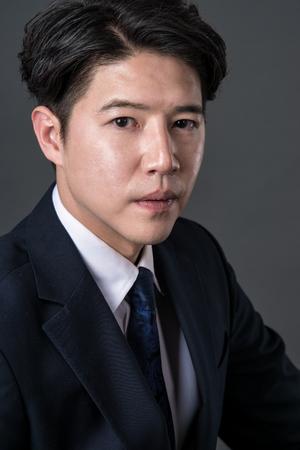 chuckle: East Asian businessman shooting studio portrait photo Stock Photo