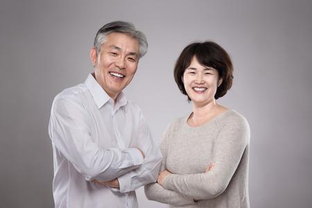 Happy Asian middle-aged couple studio portrait Foto de archivo