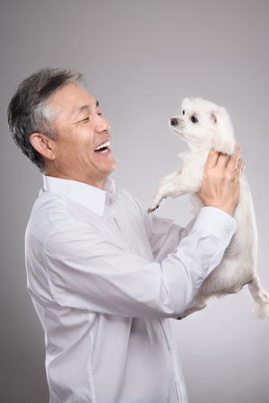 Studio portrait of Asian middle-aged male with dog