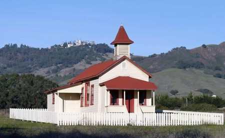 An old schoolhouse in an open field with a castle on the mountains in the background. photo