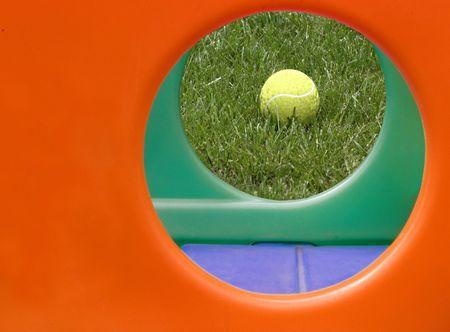 Ballon jaune encadrée par des trous circulaires d'un jeu d'enfant structure.  Banque d'images - 377070