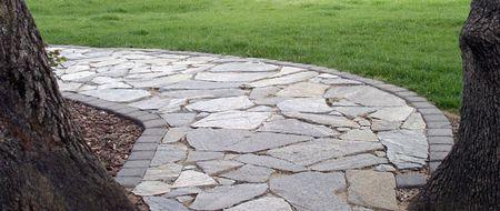 Stone allée encadrée par deux arbres et bordée de vert gazon.  Banque d'images - 384610