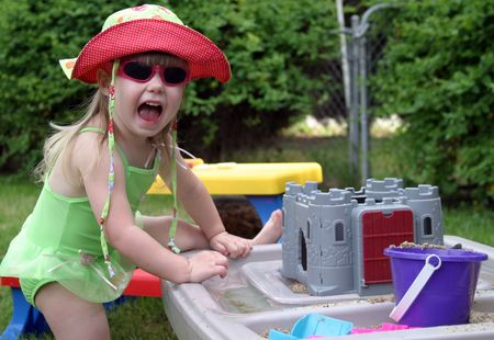 frontyard: Young toddler in swimsuit having fun playing with summer toys.