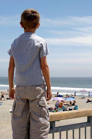 Jeune garçon, le dos à la caméra, à regarder l'activité sur la plage.  Banque d'images - 414498
