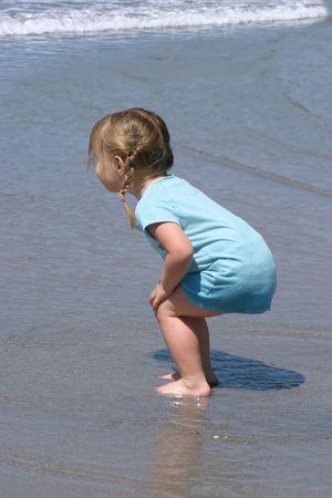 Jeune fille d'enfant en bas âge attendant une vague sur la plage. Banque d'images - 414496