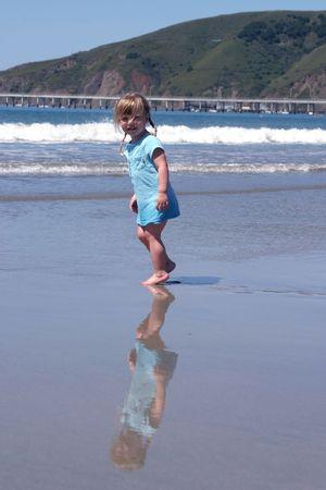 Tout-petit fille de marcher sur la plage, la réflexion sur le sable humide.  Banque d'images - 428055