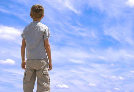 Jonge jongen zoekt up twoards blauwe hemel met wolken. Stockfoto