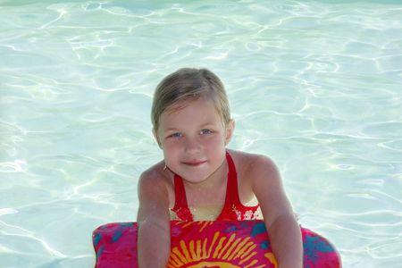 Cute petite fille dans la piscine rafraîchissante avec paddle board. Banque d'images - 5107206