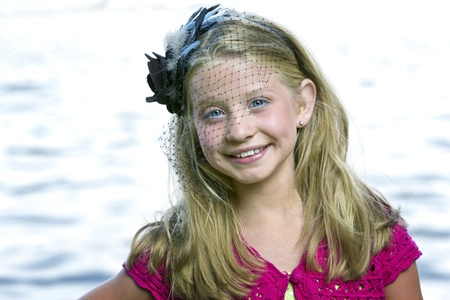 Beautiful little blue-eyed, blonde girl standing in front of sun drenched lake Foto de archivo