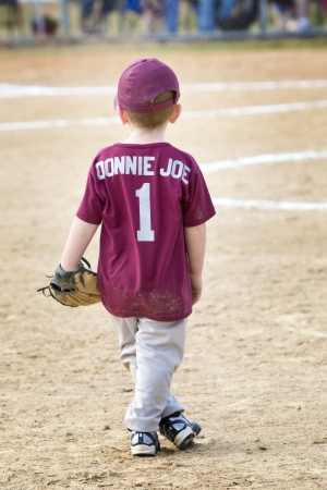 Darling little 4 year old redheaded boy in ball uniform and cap with glove standing on field photo