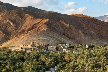 View at ruins of abandoned Birkat al Mawz, Oman, in front of mountain, date palms in front 版權商用圖片