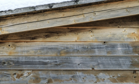 sloping: Covered sloping roof of a weathered old wooden hut with snow