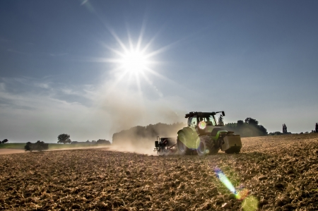 Tractor working in the field in the late afternoon photo