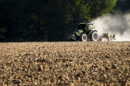 waxes: Tractor working in the field in the late afternoon
