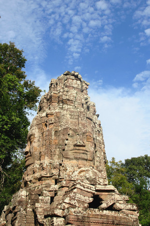 Face tower of the west gopura or entrance gate to the Ta Prohm monastery temple in Angkor area, Cambodia.