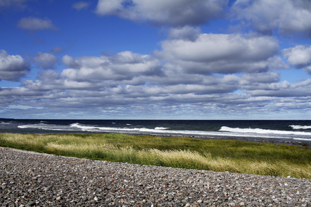 Seashore landscape with pebbles, clouds and blue sky from Lummelunda in Gotland Island, Sweden.