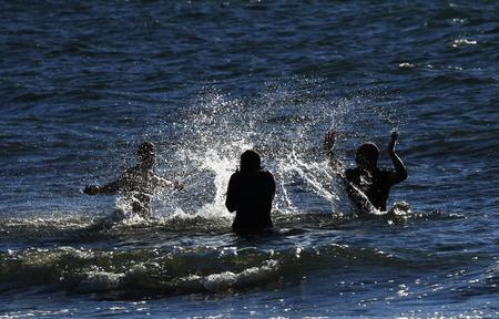 Three friends splashing water against each other in the sea in Gotland, Sweden.
