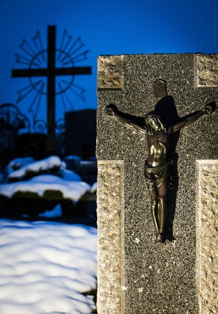all saints  day: Grave stone with a Jesus figure and a cross on All Saints Day in the Snow