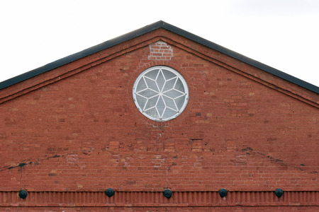 Crest of an old building with round window. Building made of bricks.