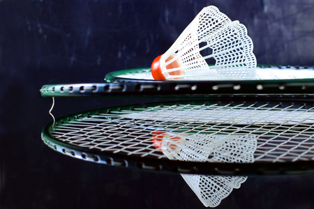 Badminton racket and shuttlecock closeup isolated on black mirroring background. Stock Photo