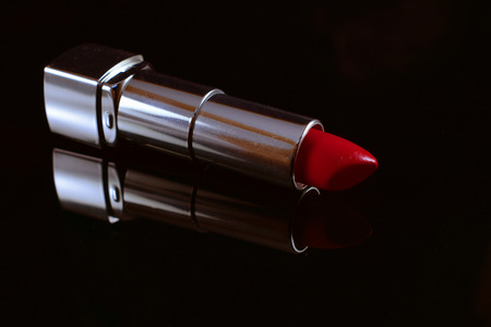 mirroring: Lipstick on mirroring table with black background. Stock Photo