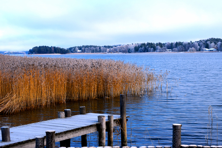 Frosty wooden pier on fall with beautiful view to sea.