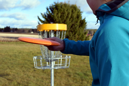 Disc golf close up. Young woman aiming near target.