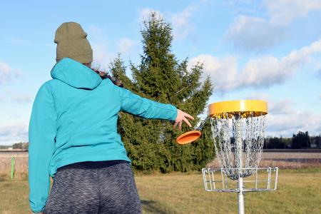 젊은 여자 디스크 골프 코스에 대상 디스크를 던지고.