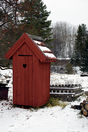 Red wooden outhouse toilet on wintertime.