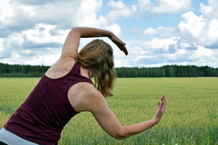 Middle aged yoga woman stretching and exercise outdoors. Rear view, field on background.