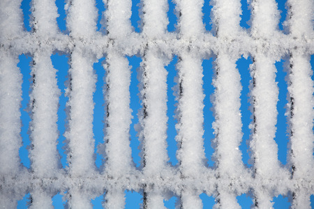 Fence covered by snow and hoarfrost photo
