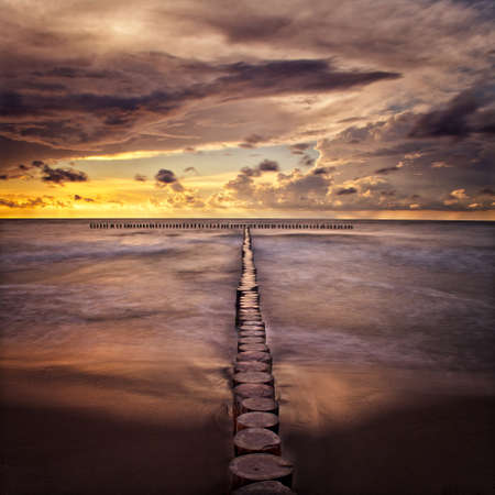 groynes: Sunset at sea composing with aligned groynes Stock Photo