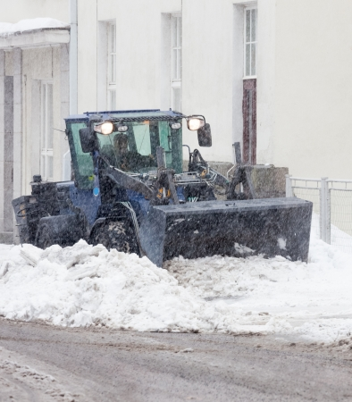 snowbanks: Snowplow cleaning a city street in snowfall Stock Photo